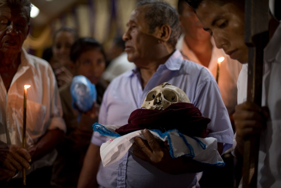 Maya Itza elders hold a skull, as they wait for heavy rain to stop, the skull will be used in the processión of The Holy Spirits. San José, Petén, northern Guatemala. Photo: Santiago Billy/Comvite