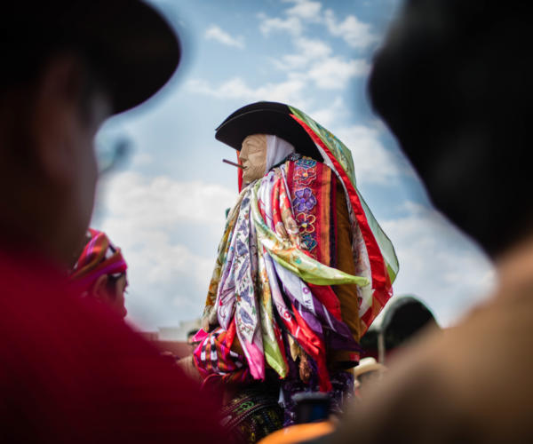 The Maximon effigy, freshly adorned with new ties and smoking a wooden cigarette, rests on the shoulders of a member of the cofradía, above the crowds who have gathered to watch. Photo: Anna Watts/Comvite