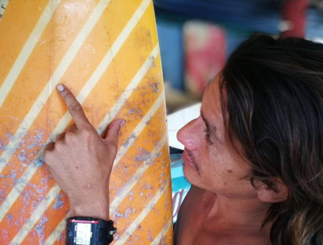 Abner Rivera, 31, checks a surfboard in his home in El Paredón. Photo: Santiago Billy/Comvite