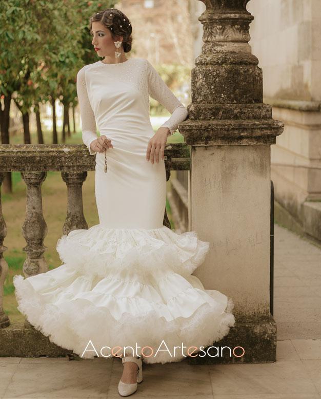 Traje de flamenca blanco de Aurora Ruíz con cuerpo drapeado hacia un lado y volantes al hilo