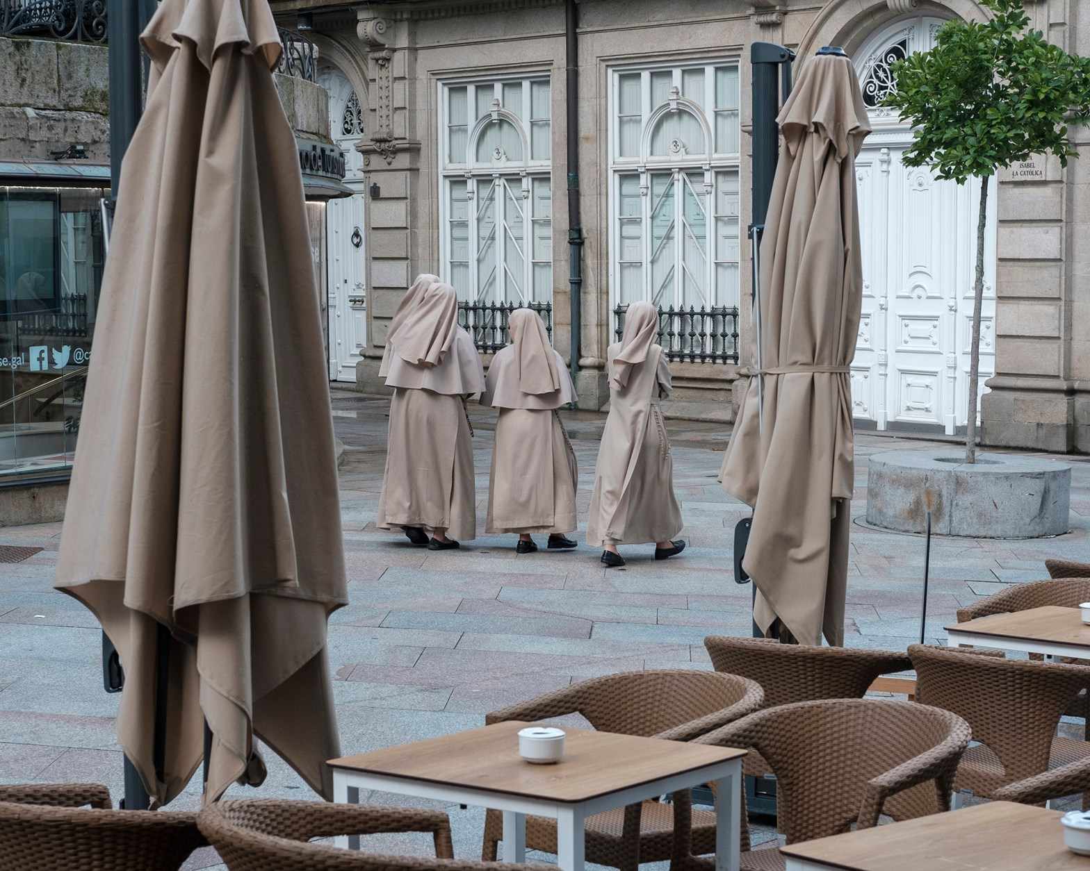 Nuns walk down the street matching the colour and texture of the canopies in the adjacent cafe