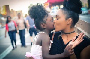 a mother kissing her daughter