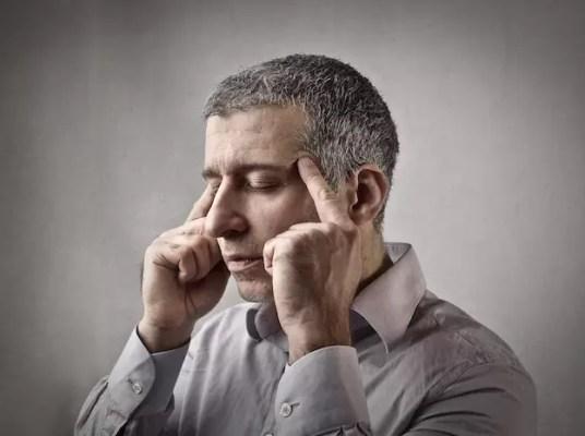 Mann hält sich konzentriert die Schläfen