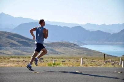 Ein Mann joggt auf der Straße, im Hintergrund sieht man einen See. Bewegung ist von essenzieller Bedeutung für deine Konzentration