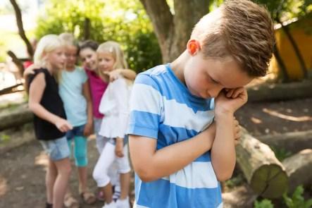 Junge wird aus Gruppe ausgeschlossen. Mädchen zeigen mit dem Finger auf ihn.