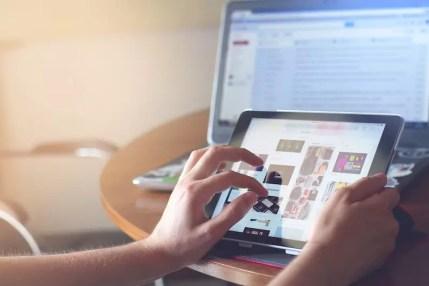 Eine Hand bedient ein Tablet, im Hintergrund sieht man einen Computer Bildschirm