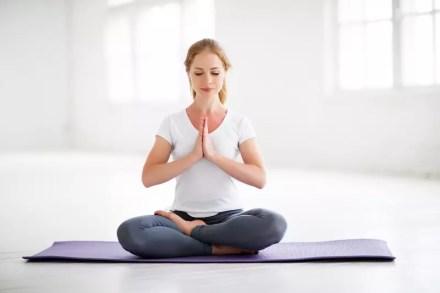 Frau sitzt auf einer Matte und meditiert