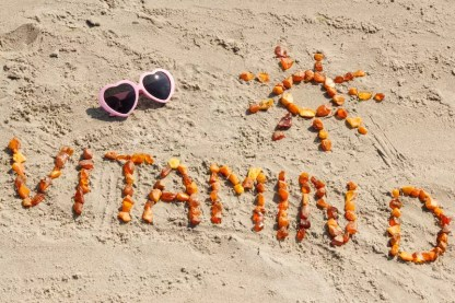 Eine Sonnenbrille im Sand, darunter ist Vitamin D geschrieben