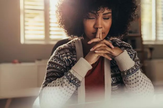 Frau sitzt konzentriert bei der Arbeit am Tisch, hat die Augen geschlossen und sammelt Gedanken