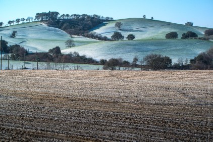 Colline verdi e campi marroni imbiancati dalla neve