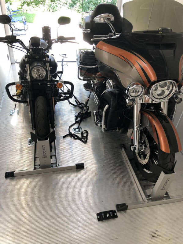 One small and one large motorcycle in wheel chocks on a trailer