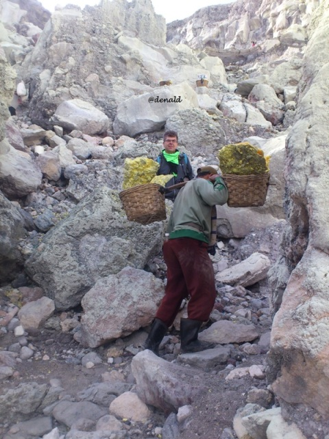 Penambang dengan membawa belerang menaiki lereng dari kaldera menuju bagian atas kawah