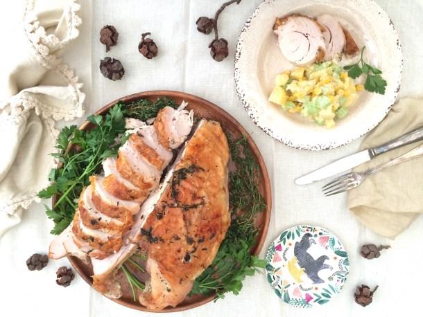 Pechuga de Pavo al horno, la mitad rebanado, sobre un plato con hierbas frescas