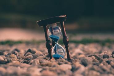 hourglass on rocky ground
