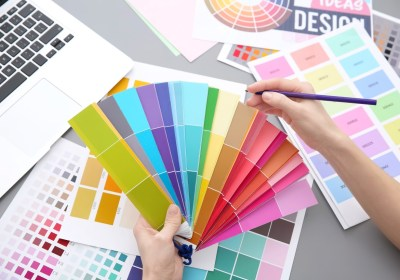 Young designer choosing color of interior while working in offic