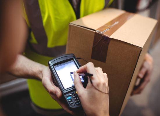 A courier wearing a high-visibility vest and holding a brown cardboard box and an e-signature reader awaits a signature from the recipient of the delivery.