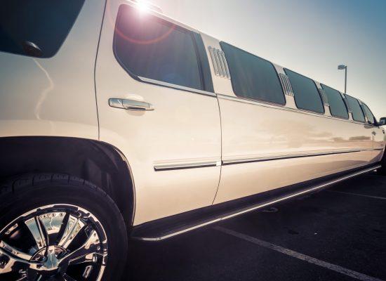 A white stretch limousine parked across a car park under a clear blue sky.