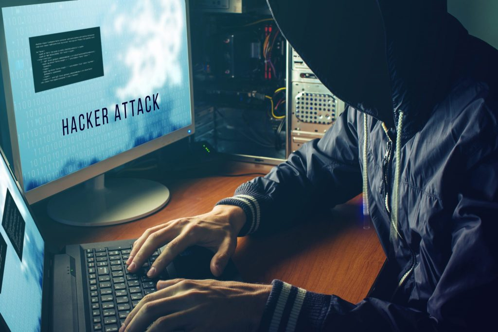 A man wearing a windbreaker jacket with his face obscured beneath the hood is sitting alongside a PC and laptop; the screen displays that he is hacking the system.