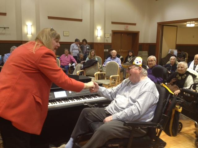 Disabled senior shakes hands with a woman in front of a piano.