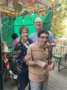 Barbara Ginsburg, Kevin Ginsburg and Harry Wenkert standing outside the sukkah.