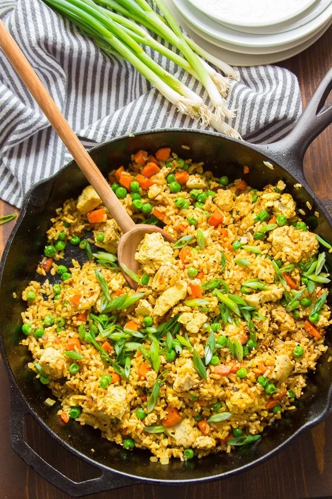 Skillet Filled with Curry Fried Rice with Serving Spoon