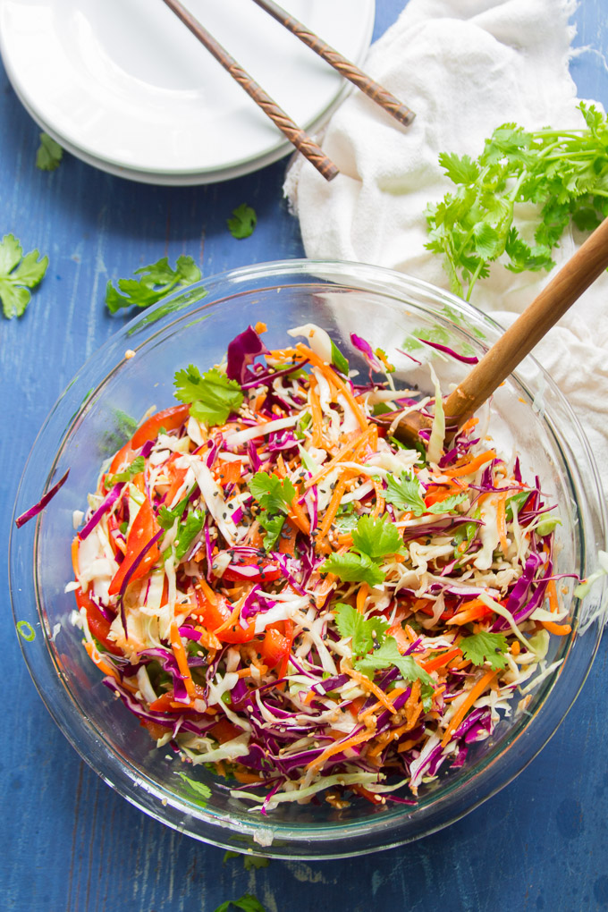 Asian Slaw in a Bowl with Napkin, Wooden Spoon and Stack of Plates