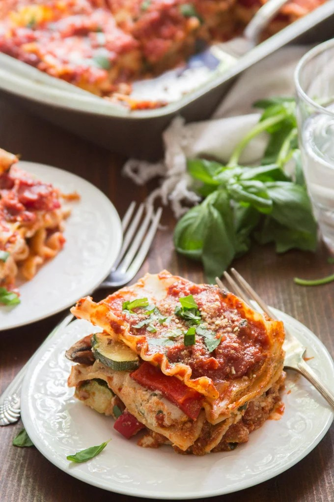 Vegan Lasagna on a Plate with Fresh Basil, Water Glass and Baking Dish in the Background