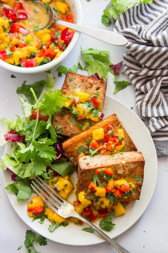 Grilled Tofu, Mango Salsa and Fresh Greens on a Plate with Fork and Striped Napkin
