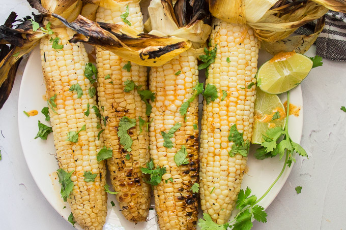 Close Up of 4 Ears of Mexican Grilled Corn Topped with Fresh Cilantro