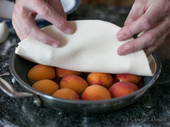 Cover the apricots and tuck in the sides.