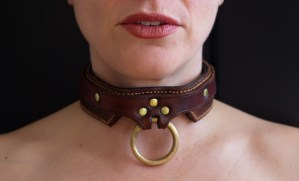 A person wearing an ornate leather collar.