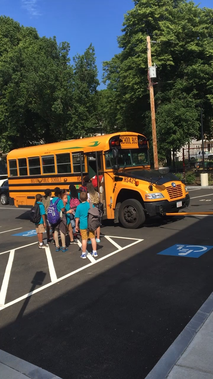 A video of children in teal shirts getting on the bus at the end of the day