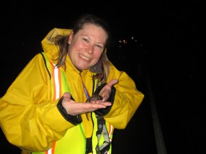 Karen Ruzycki gives a salamander a lift.  Photo: M. Hall