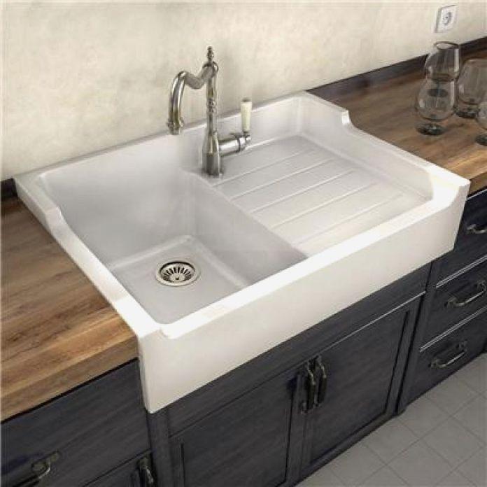 Un évier en céramique blanc posé sur un meuble de cuisine.