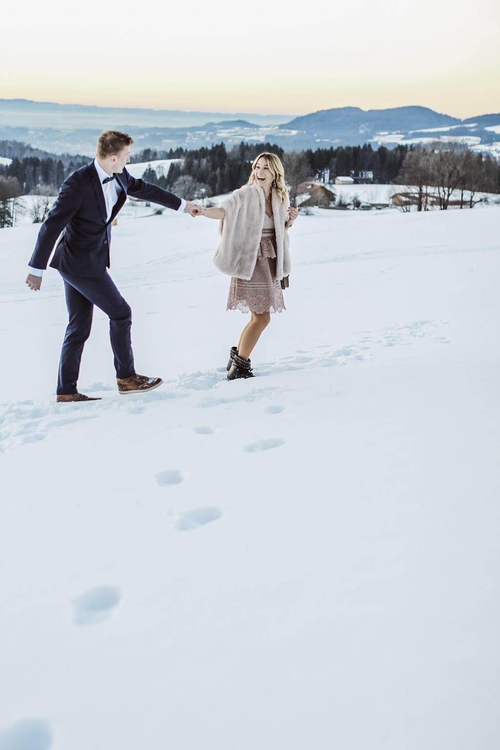 Georg Teigl und Karin Kaswurm laufen lachend durch den Schnee