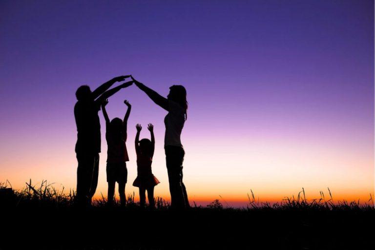 Uma família, pai, mãe e dois filhos com os braços para cima, num campo ao por do sol.