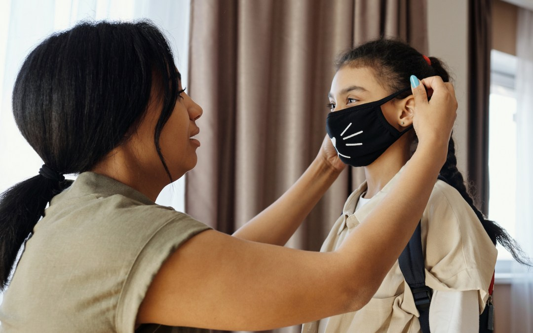 Mother putting a mask on her daughter before heading to school