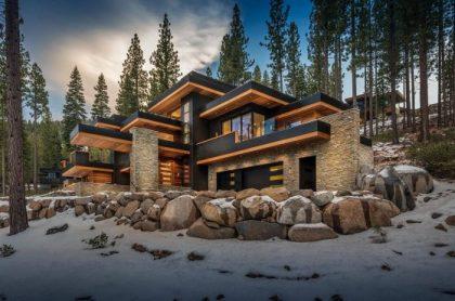 Taşı bir kaplama ve ahşap ve gri detaylar olarak vurgulayan düz çatılı büyük ve lüks bir evin tasarımı