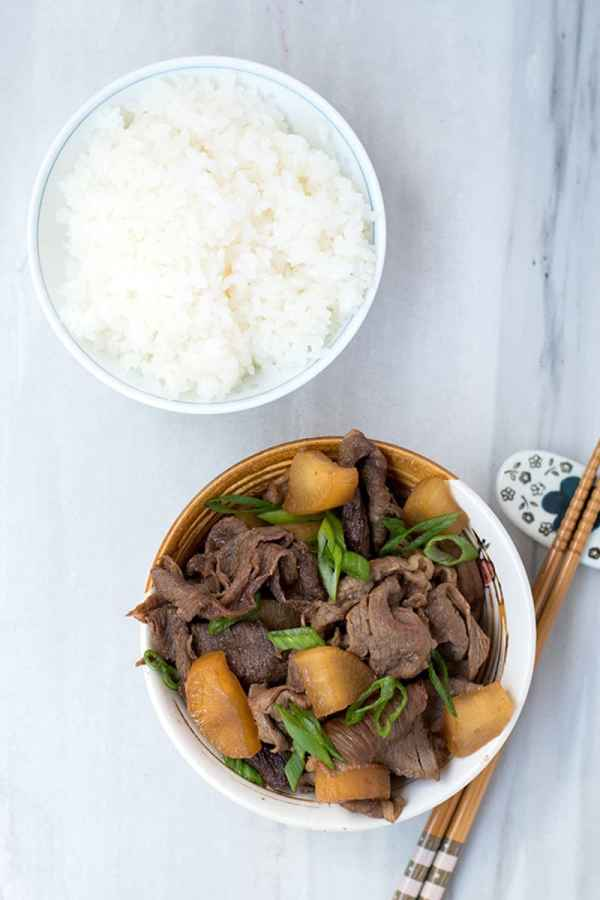 Top view of a bowl of beef with daikon radish with a bowl of rice and chopsticks next to it.