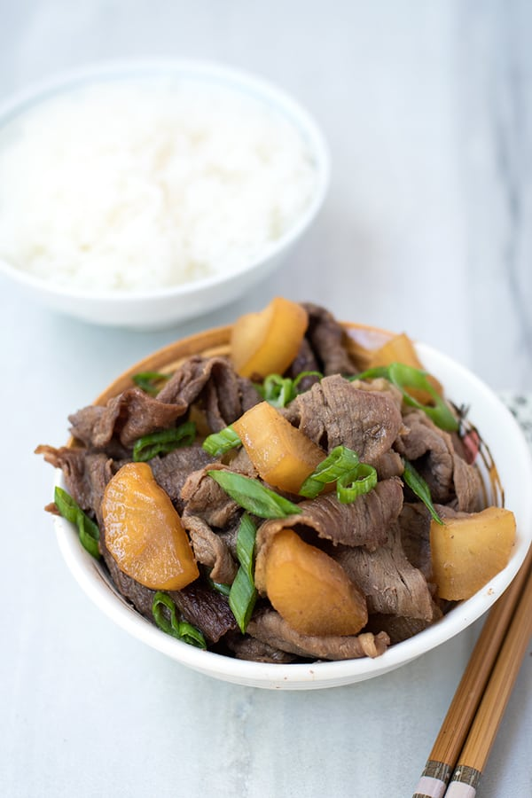 Bowl of beef with daikon radish topped with sliced green onion, with a bowl of rice.