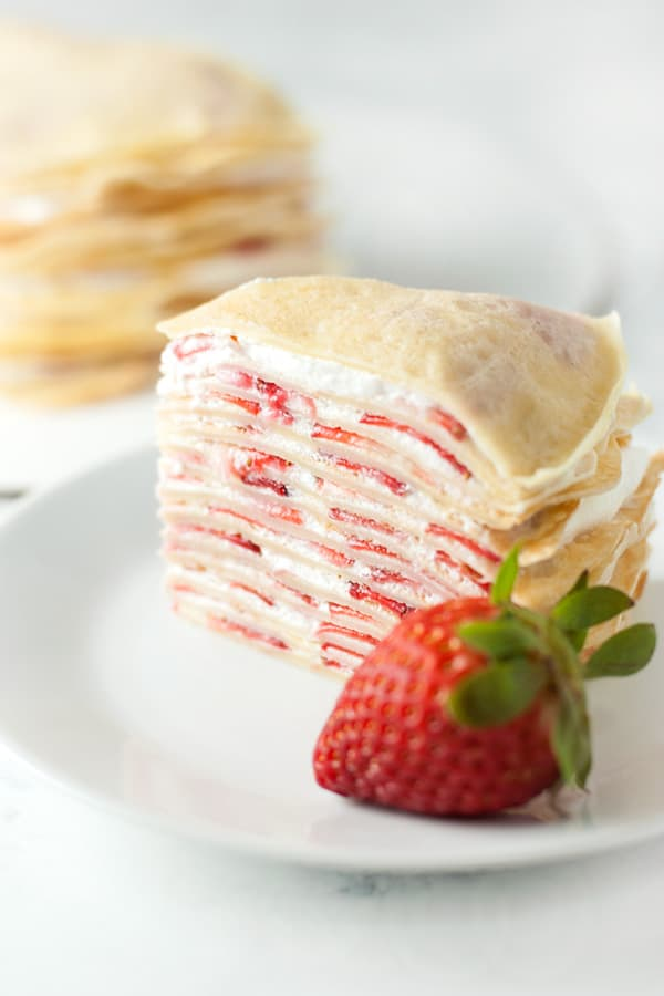 Strawberry Crepe Cake-Filled with whipped cream and strawberries, this fancy looking strawberry crepe cake comes together easily to make an impressive and delicious dessert.