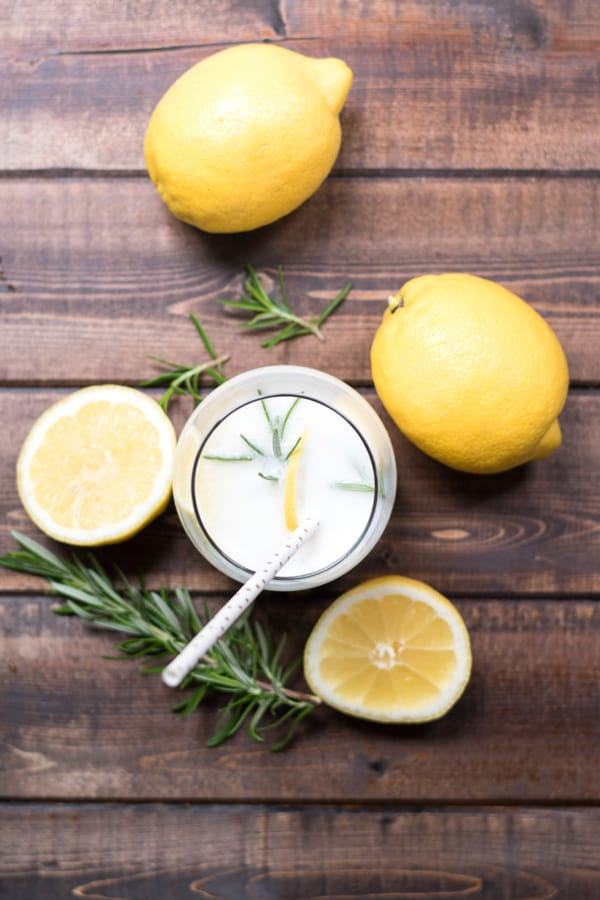 Top view of a glass of rosemary lemon cream soda with lemons and sprigs of fresh rosemary.