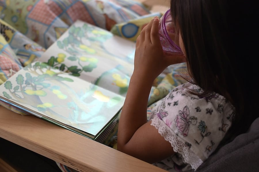 Child drinking bedtime tea for kids while reading picture book.