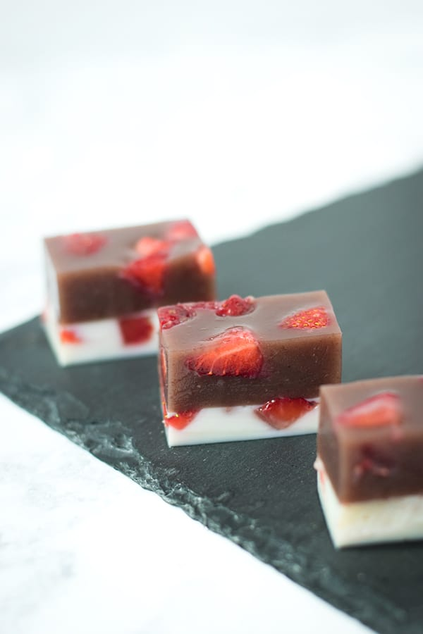Strawberry and Milk Yokan cut into rectangles and lined up on black slate.