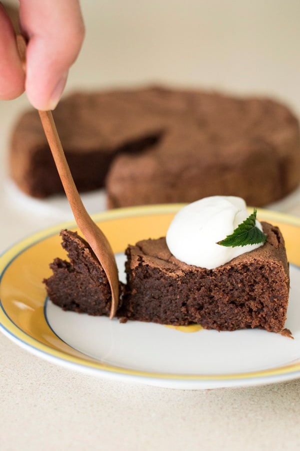 Taking a bite from gluten free French chocolate cake topped with dollop of cream using wooden fork.