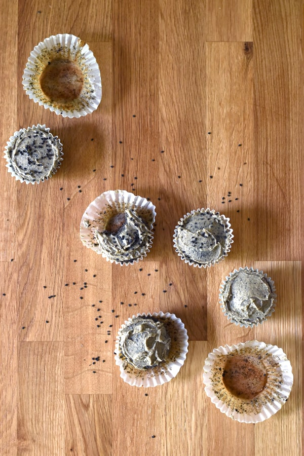 Top down view of black sesame cupcakes with peanut butter frosting and empty cupcake liners.