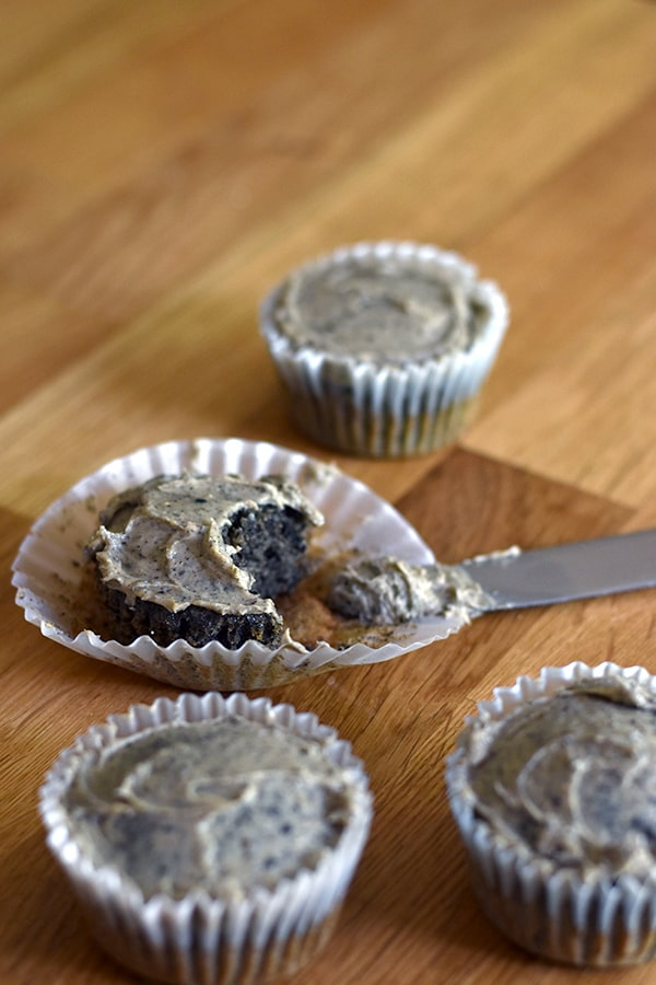 Black sesame cupcakes with peanut butter frosting with one cupcake with a bite taken out of it.