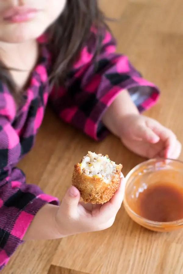 Little girl holding a round korokke, with tonkatsu sauce.