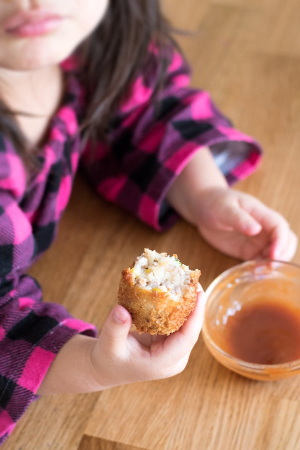 Little girl holding a round korokke dipped in the tonkatsu sauce.