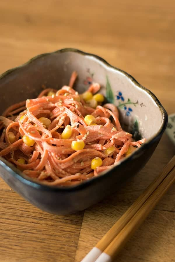 carrot salad in a bowl with chopsticks next to it.
